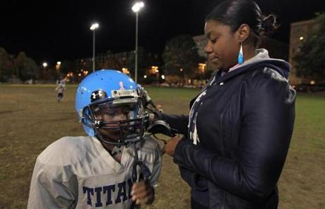 Chauntae Robinson straps a newer helmet with more padding onto her 9-year-old son, Andre, who had a mild concussion last month.